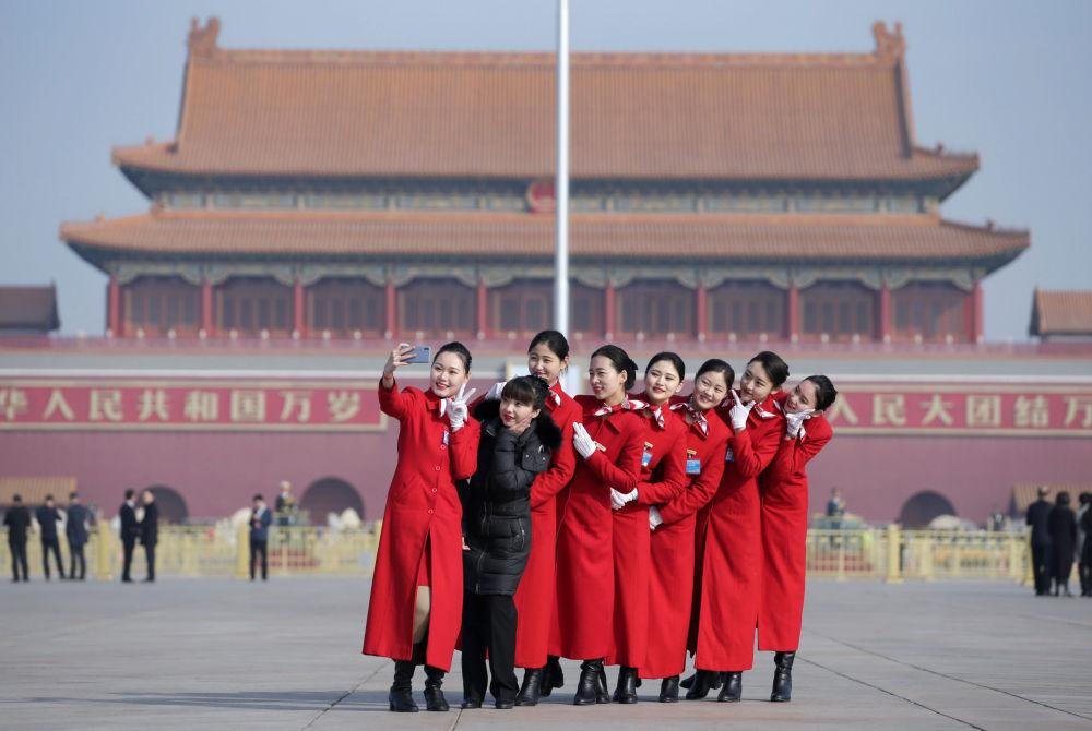 Güzelliğiyle dikkatleri üzerinde toplayan Çinli  hostes kızları, Pekin'deki Tiananmen Meydanı'nda.