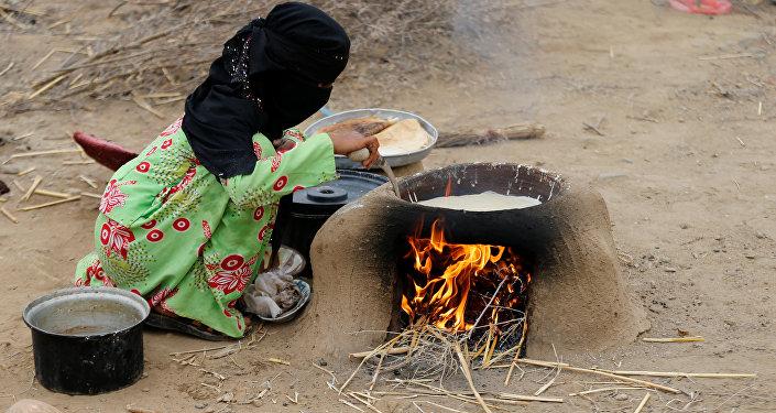 Yemen'in kuzeybatısındaki Hacca eyaletinin Abs kenti yakınında savaşta evsiz, yersiz kalanların oluşturduğu kampta bir kadın elde olanlarla yemek pişirmeye çalışıyor.