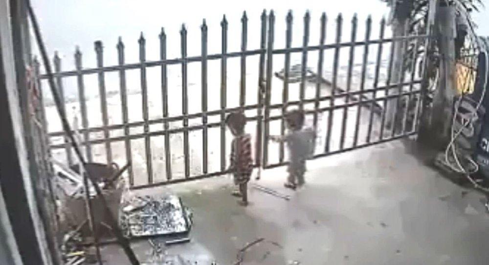 Tayland'da evin bahçe kapısından çıkan çocuklar