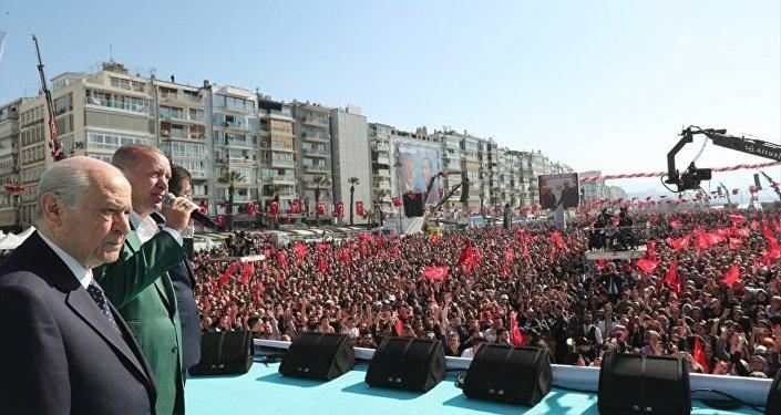 AK Parti-MHP İzmir ortak mitingi, Türkiye Cumhurbaşkanı ve AK Parti Genel Başkanı Recep Tayyip Erdoğan (ortada) ile MHP Genel Başkanı Devlet Bahçeli (solda) ve AK Parti İzmir Büyükşehir Belediye Başkan Adayı Nihat Zeybekci'nin de (sağda) katılımıyla Gündoğdu Meydanı'nda gerçekleştirildi.