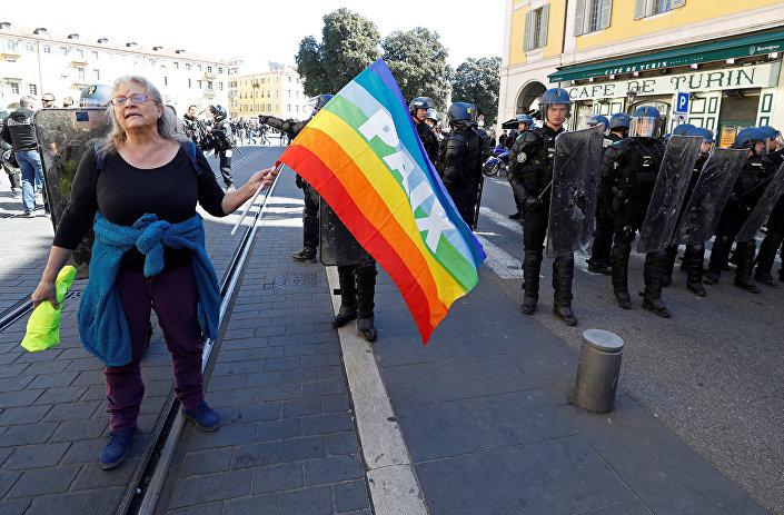 Sosyal adalet için mücadele eden Attac grubunun bir üyesi olan Genevieve Legay, elinde barış yazan gökkuşağı bayrağıyla barışçı şekilde yürüyordu.