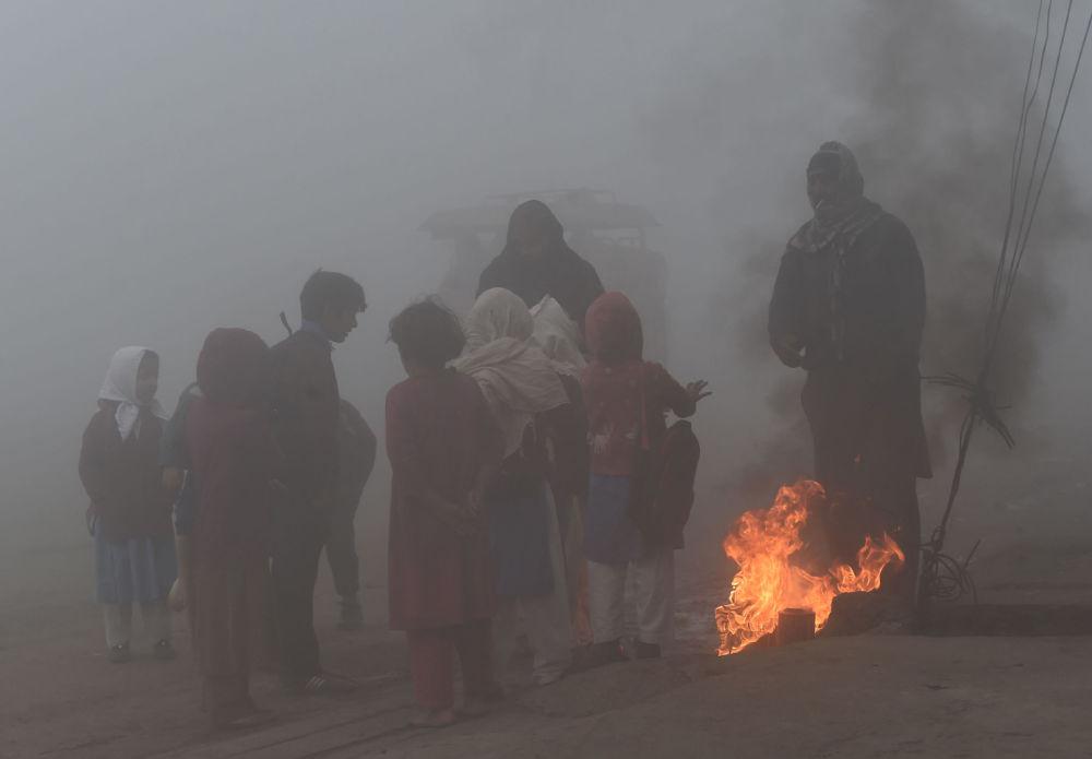 Pakistan'ın Lahor kentinde ateşin yanında ısınmaya çalışan okul öğrencileri.