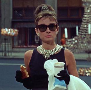 Truman Capote'ın romanından uyarlanmış 1961 yapımı Breakfast at Tiffany's  filminde Holly Golightly karakteriyle klasikleşmiş bir moda figürüne dönüşen Audrey Hepburn, 'küçük siyah elbise'nin miladı kabul edilen Givenchy elbisesiyle, sadece dönemine değil tüm zamanlara damgasını vuruyor.