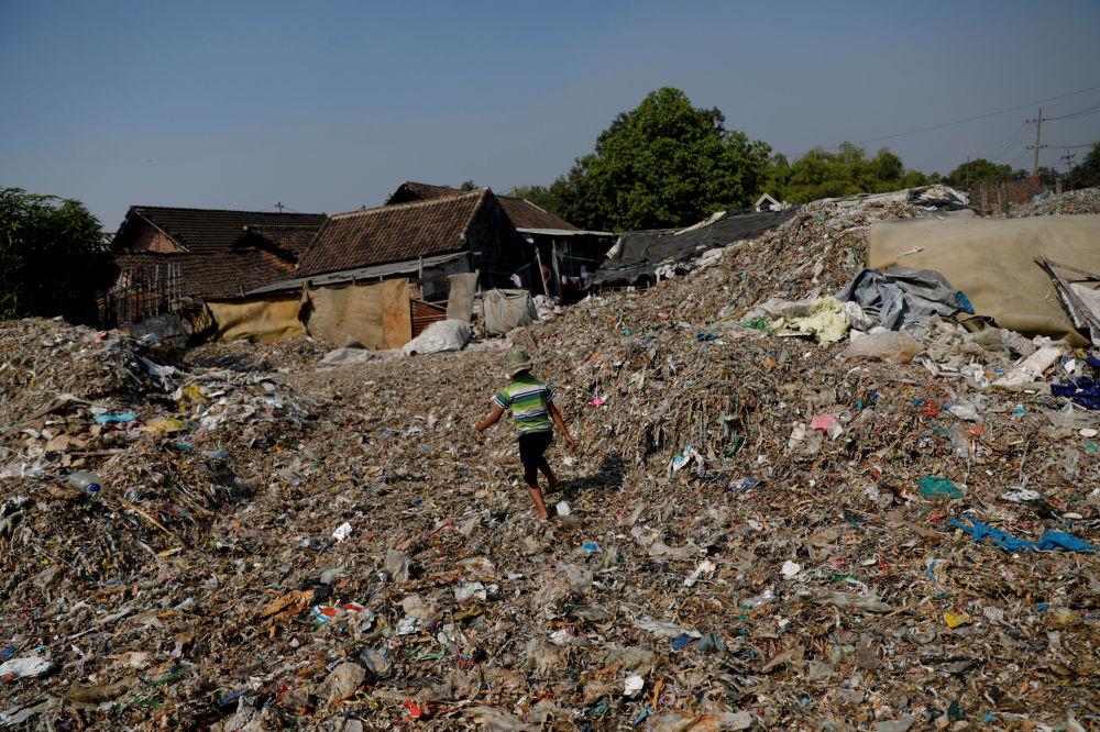 Bangun'daki evlerin ön ve arka bahçelerinde bir zamanlar pirincin yetiştiği topraklar çöp atıklarıyla dolu.