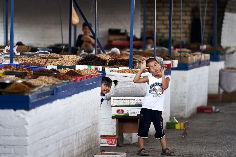 Kırgızistan'daki bir pazar yerinde saklambaç oynayan çocuklar.