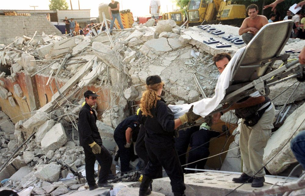 Yunan kurtarma ekipleri, yıkılan binalarda arama çalışmalarını yürütürken.
