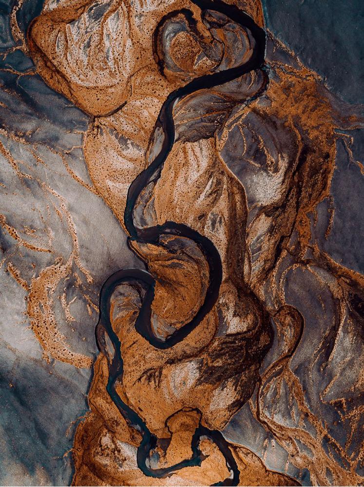 Hegen'in İzlanda'daki buzulların erimesiyle siyah volkanik kumların nehirlere dökülmesinin görüntülendiği bir karesi.