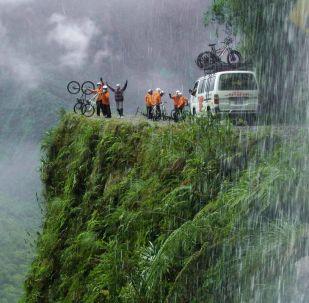 """Olağandışı sürüş koşullarından dolayı Bolivya'daki Yungas yolu """"Ölüm Yolu"""" olarak adlandırıldı. Yungas yolunun bulunduğu  Bolivya'nın başkenti La Paz,  dünya'nın en yüksek rakımına sahip başkentleri arasında yer alıyor. Yungas yoluna ulaşılması için 4.650 metre yüksekliğe çıkmak gerekiyor. Yolun """"Ölüm Yolu"""" olarak adlandırılmasının sebebi, her yıl 200 ila 300 kişinin burada can vermesinden kaynaklanıyor. Buna rağmen tur şirketleri bu yolda yokuş aşağı ekstrem sporla uğraşan bisikletçileri götürmeye devam ediyor."""