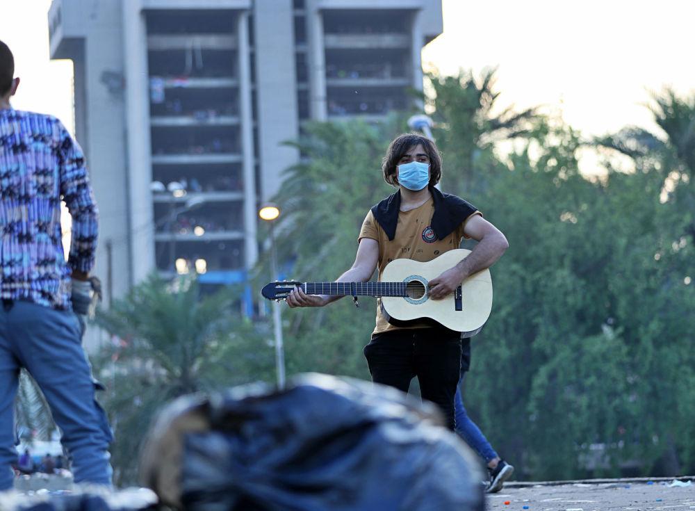 Irak'ın başkenti Bağdat'taki Tahrir Meydanı'nda toplanan göstericilerden biri, gitar çalıyor.