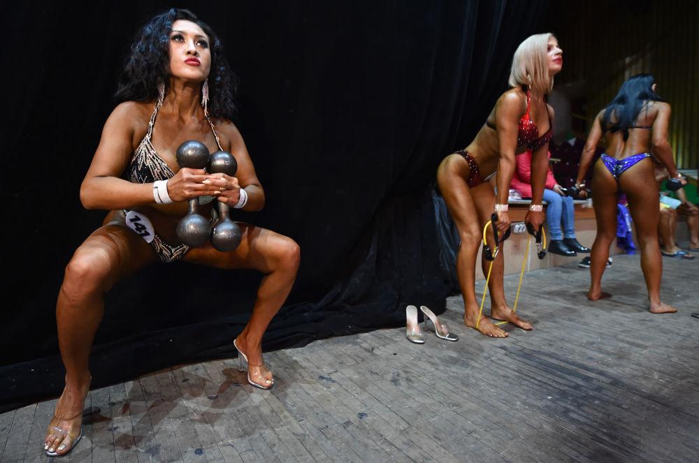 Sahne arkasında ısınma hareketlerini yapan kadın katılımcılar.