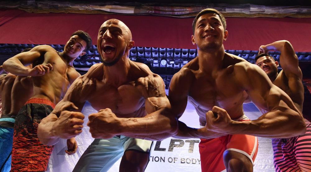 Bişkek'te gerçekleşen Vücut Geliştirme Yarışması'nın  erkek katılımcıları, sahneye çıkmadan önce poz veriyor.