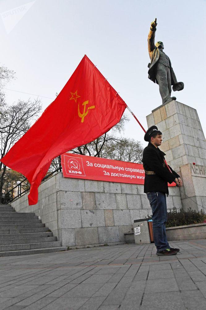 Vladivostok kentinde düzenlenen gösteri katılımcılarından biri, Ekim Devrimi'nin lideri ve Sovyetler Birliği'nin kurucusu Lenin anıtının yanında dururken...