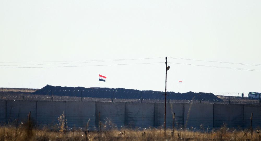 Sınırın Suriye tarafında Suriye bayrakları görülüyor.