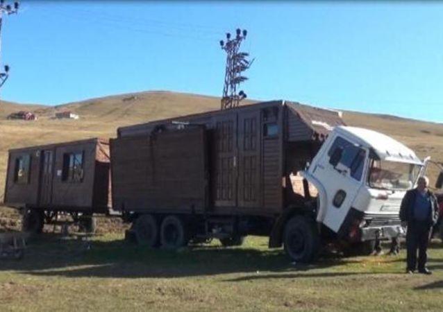Trabzon'da yaylada ev yapmak isteyen ama yapılaşma yasağına takılan Birinci 20 metrekarelik ahşap evini kamyon kasasına monte etti. Yıkım olacağı durumlarda kamyon üzerindeki gecekondusuyla yayladan ayrılan Birinci'nin ilginç yöntemi, başrolünü Kemal Sunal'ın oynadığı 'Gülen Adam' filmindeki ev taşıma sahnesini akıllara getirdi.