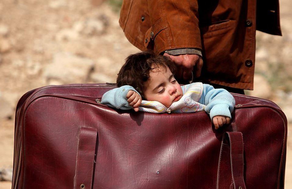 Suriye Guta'dan duygu yüklü bir an…  15 Mart 2018'de çekilen karede son 4 haftada 1,220 sivilin öldürüldüğü bölgeden kaçan bir mülteci babanın elindeki valizde taşıdığı uyuyan küçük çocuğu…