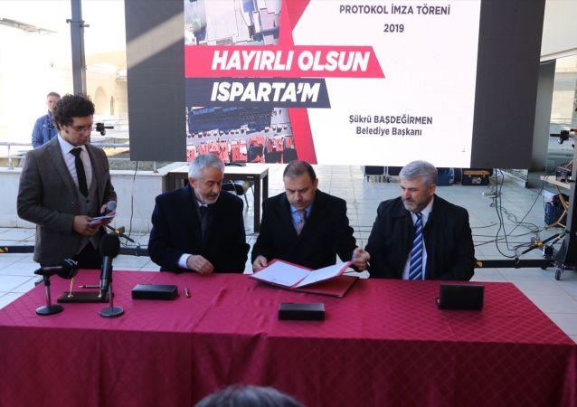 Isparta'da yaklaşık 22 yıldır bitirilemeyen Ticaret ve Kültür Merkezi inşaatının tamamlanabilmesi için Tasarruf Mevduatı Sigorta Fonu (TMSF) Başkanı Muhiddin Gülal (sa2) ile Isparta Belediye Başkanı Şükrü Başdeğirmen (sağ3) arasında protokol imzalandı.