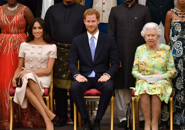FILE PHOTO: Britain's Queen Elizabeth, Prince Harry and Meghan, the Duchess of Sussex, pose for a picture at in London, Britain June 26, 2018. John Stillwell/Pool via Reuters/File Photo