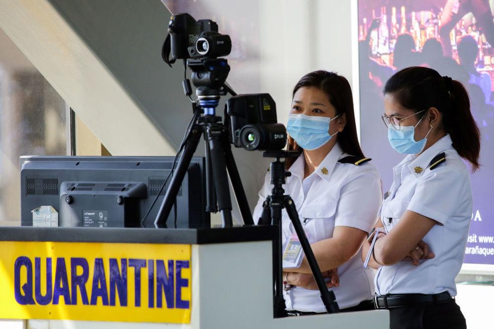 Filipinler'deki Ninoy Aquino Havalimanında Çin'den  gelen yolcular termal tarayıcılardan geçiriliyor.