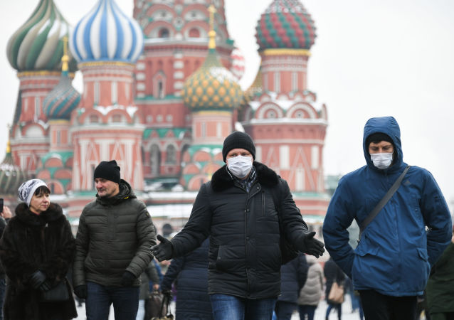 Chinese tourists wearing protective masks walk at Red Square, in Moscow, Russia. The coronavirus outbreak has killed at least 259 people and infected close to 12,000 people globally, as it continues to spread.