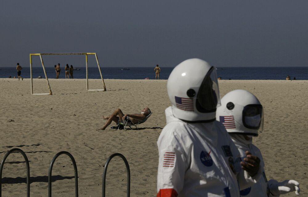 Tercio ve Aliceia Galdiono çifti Kovid-19'dan korunmak için astronot kıyafeti giyerek sahilde gezdi.
