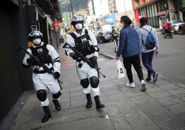 Kolombiya devletinin güvenlik güçleri, uluslararası kısaltması 'hazmat' olan tehlikeli maddelerden koruyan takım giyerek devriye geziyor.