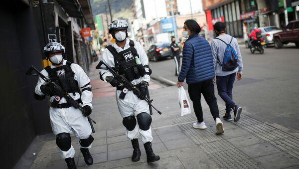 Kolombiya devletinin güvenlik güçleri, uluslararası kısaltması 'hazmat' olan tehlikeli maddelerden koruyan takım giyerek devriye geziyor.  - Sputnik Türkiye