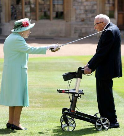 Kraliçe 2. Elizabeth karşısında yürüteçe tutunarak duran Tom Moore'u babası Kral 6.George'un kılıcıyla dokunmak suretiyle şövalye ilan etti.