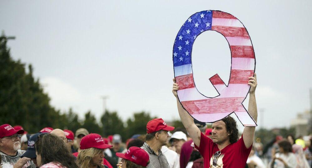 QAnon komplo teorisine atfen Q amblemi tutan bir yandaş Trump mitingine girmeye çalışırken (Wilkes-Barre, Pa., Ağustos 2018)