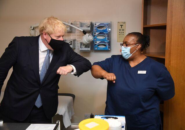 Boris Johnson tıbbi merkez ziyaretinde sağlık çalışanlarıyla selamlaşırken