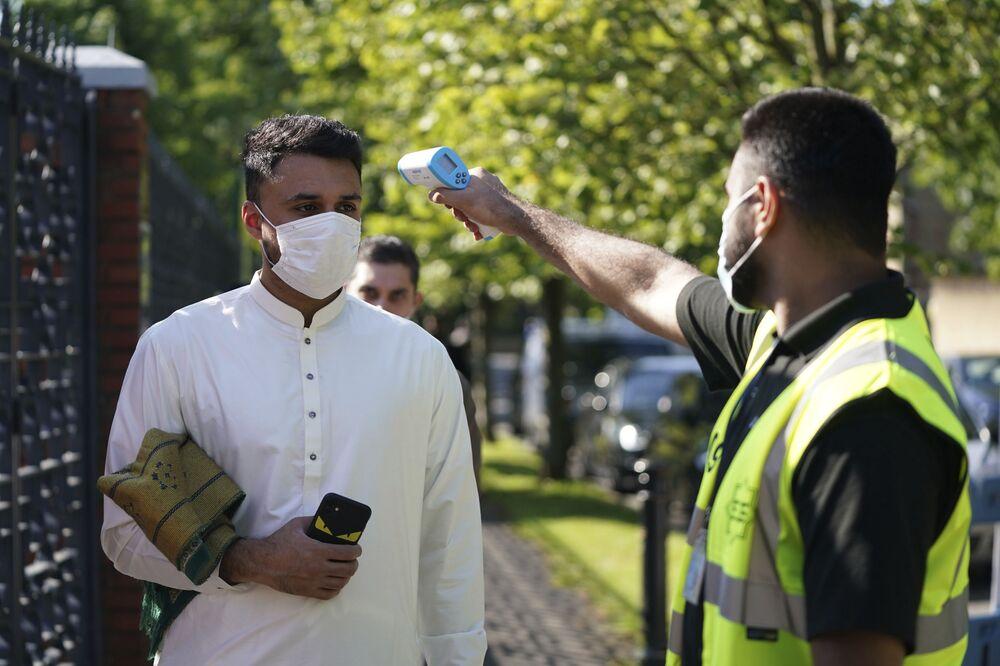 İngiltere'nin Manchester kentindeki Merkez Camisi'ne bayram namazı için  gelen Müslüman'ın ateşi ölçülüyor