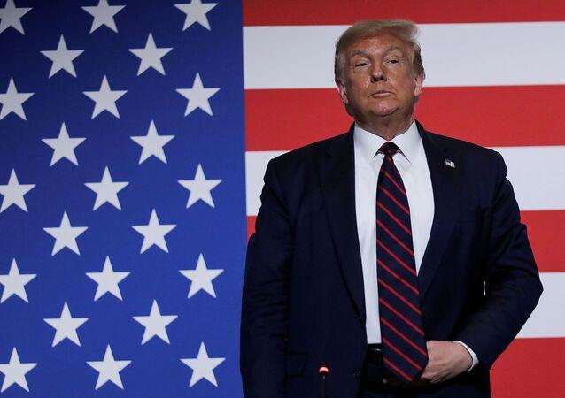Kızılhaç merkezini ziyaret ederken ABD bayrağı önünde duran Başkan Donald Trump