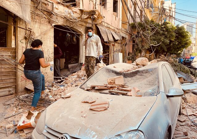 People wearing face masks walks past damaged cars after Tuesday's massive explosion in Beirut, Lebanon. The blast hit Lebanese capital on August 4, with over 80 people killed and some 4,000 injured.