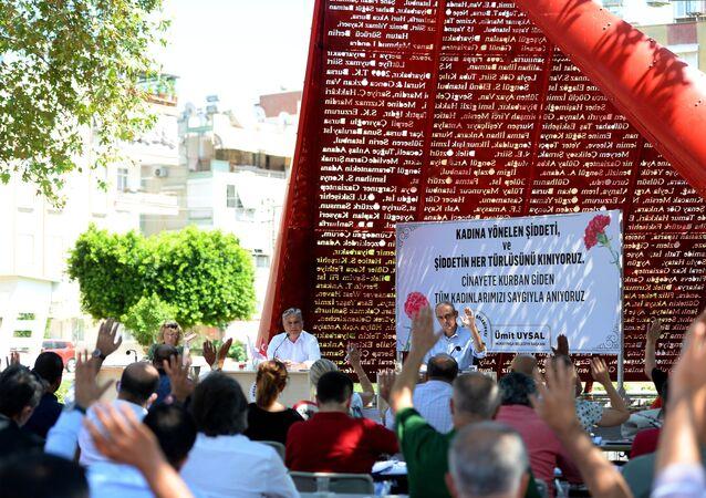 Muratpaşa Belediyesi Meclisi, artan kadın cinayetlerine dikkat çekmek için, üzerinde öldürülen kadınların adının yazılı olduğu 6 metrelik Al Yazma Anıtı önünde toplandı.