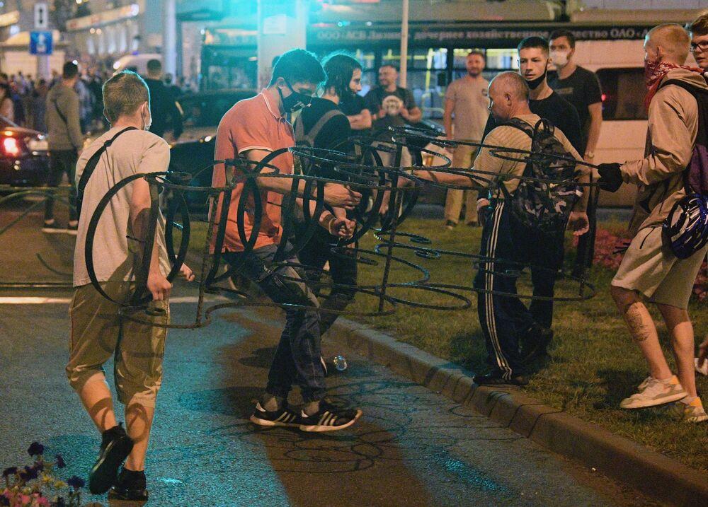 Minsk'teki protestoların katılımcıları, barikat kurarken...