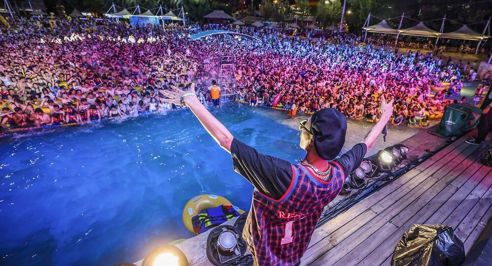 Vuhan Maya Plaj Suyu Parkı'nda düzenlenen elektronik müzik festivaline katılan binlerce kişi, balık istifi şekilde maske ve hiçbir güvenlik tedbiri olmadan havuzlara doluştu.