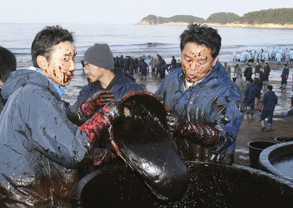2007 yılında vinç mavnası ile Hepei Spirit petrol tankeri  Güney Kore kıyılarında çarpıştı ve 2.8 milyon galon ham petrol denize döküldü. Kaza sonucu Taen kasabasının batısında 160 kilometrelik bir sahil şeridini etkileyen büyük çaplı bir kirlilik oluştu. Fotoğrafta: Kasaba sakinlerinden oluşan  gönüllü gruplar, sahilde temizlik çalışmalarını sürdürüyor, 2007