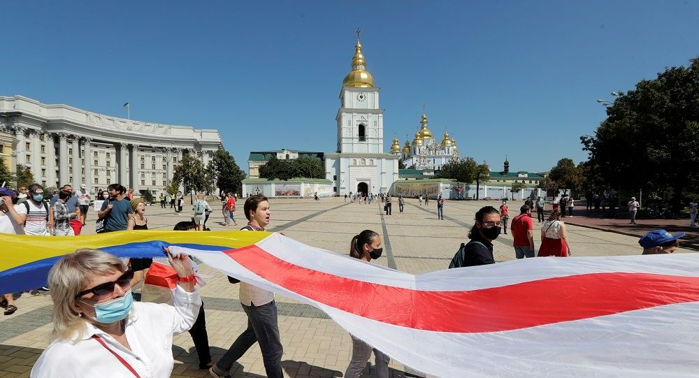 People carry the historical white-red-white flag of Belarus and the Ukrainian national flag during a rally in support of the Belarusian opposition