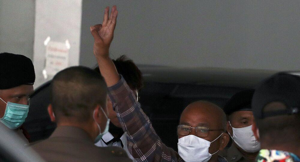 Tayland polisinin gözaltına aldığı demokrasi yanlısı protestocu, Bangkok'ta polis merkezine sokulması sırasında üç parmak selamı verirken