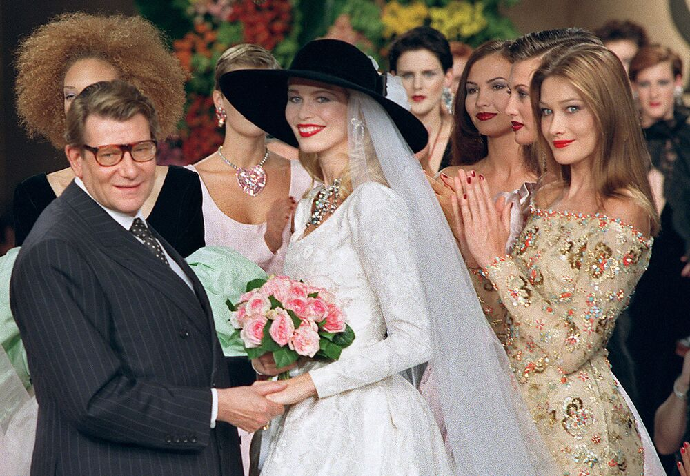 """Parisli modacı tarafından bir gece kulübünde dans ederken tesadüfen keşfedildiğini söyleyen Schiffer, """"Davet üzerine içimdeki şüpheyle Paris'e gittim. Sonra şehrin her yerine fotoğraflarım asılınca biraz utandım ama hoşuma da gitti"""" dedi. Fotoğrafta: Claudia Schiffer ve Fransız moda tasarımcısı Yves Saint Laurent, Paris'teki defile sırasında, 1996"""