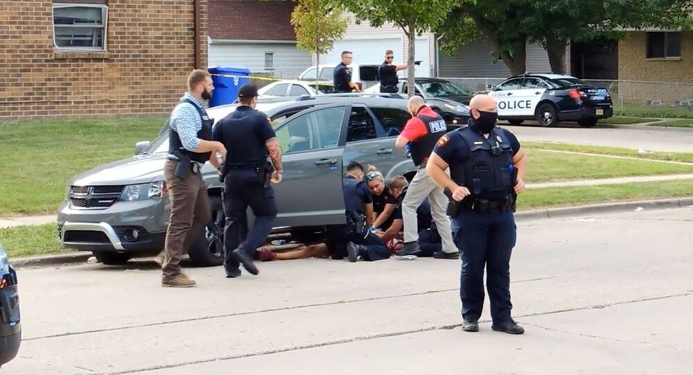 Jacob Blake lies on the street after he got shot following a police shooting in Kenosha, Wisconsin
