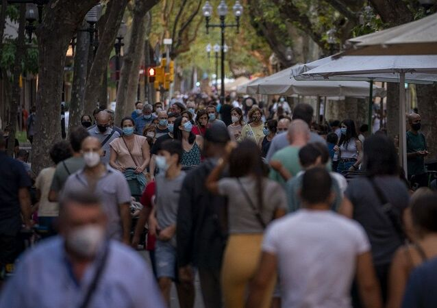 People wearing face masks walk along a boulevard in Barcelona, Spain