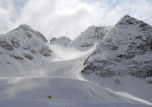 A rescue helicopter is seen where an avalanche occurred, covering four people, in the Marmolada mountain, in northern Italy,