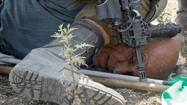 Bir İsrail askeri, Batı Şeria'da Yahudi yerleşimlerini protesto eden 60 yaşındaki Filistinli aktivist Hayri Hanun'u yere yatırdıktan sonra 50 saniye boyunca dizini boynuna bastırırken ve kelepçelerken görüntülendi. - Sputnik Türkiye