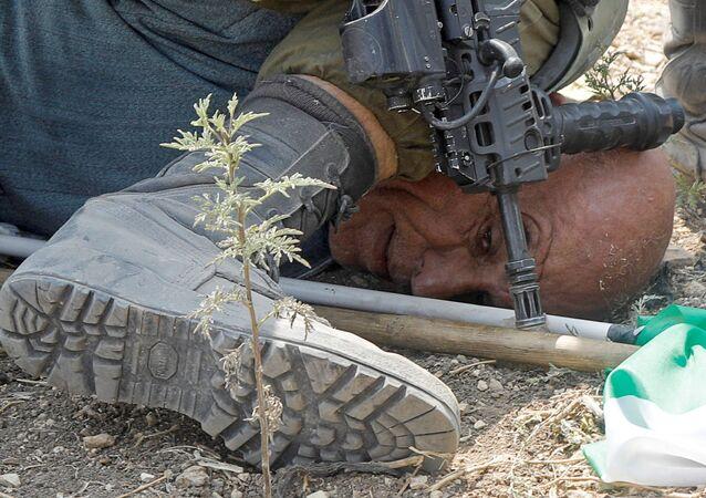 Bir İsrail askeri, Batı Şeria'da Yahudi yerleşimlerini protesto eden 60 yaşındaki Filistinli aktivist Hayri Hanun'u yere yatırdıktan sonra 50 saniye boyunca dizini boynuna bastırırken ve kelepçelerken görüntülendi.
