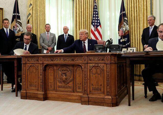 Sırbistan Cumhurbaşkanı Aleksandar Vucic (solda) ile Kosova Başbakanı Avdullah Hoti (sağda), ABD Başkanı Donald Trump'ın katıldığı törende 'ekonomik normalleşme' anlaşması imzalarken