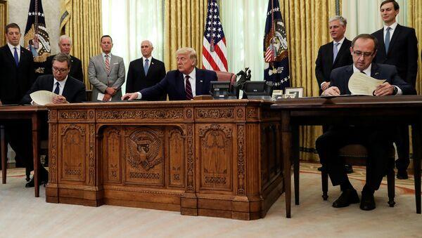 Sırbistan Cumhurbaşkanı Aleksandar Vucic (solda) ile Kosova Başbakanı Avdullah Hoti (sağda), ABD Başkanı Donald Trump'ın katıldığı törende 'ekonomik normalleşme' anlaşması imzalarken - Sputnik Türkiye