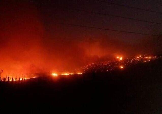Suriye'de Lazkiye kentinin doğusunda çıkan yangın Hama kırsalına doğru yayılmayı sürdürüyor.