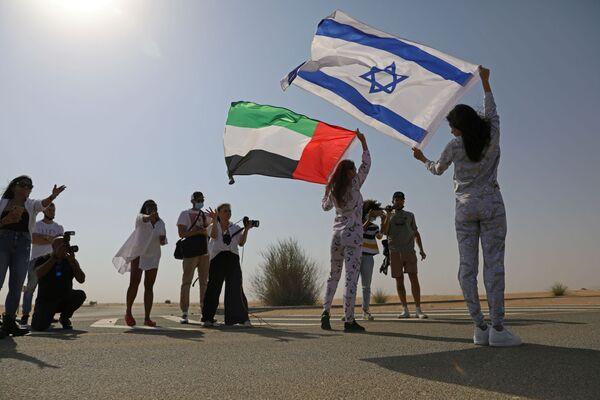 İsrail bayrağını omzunda taşıyarak Dubai'nin çöl bölgelerinde poz veren Tager'e, burada ikamet eden Rus Anastasia Bandarenka de BAE bayrağı ile eşlik etti.  - Sputnik Türkiye
