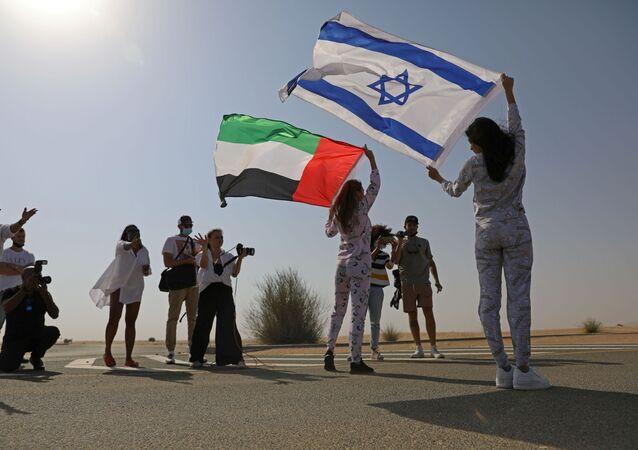 İsrail bayrağını omzunda taşıyarak Dubai'nin çöl bölgelerinde poz veren Tager'e, burada ikamet eden Rus Anastasia Bandarenka de BAE bayrağı ile eşlik etti.