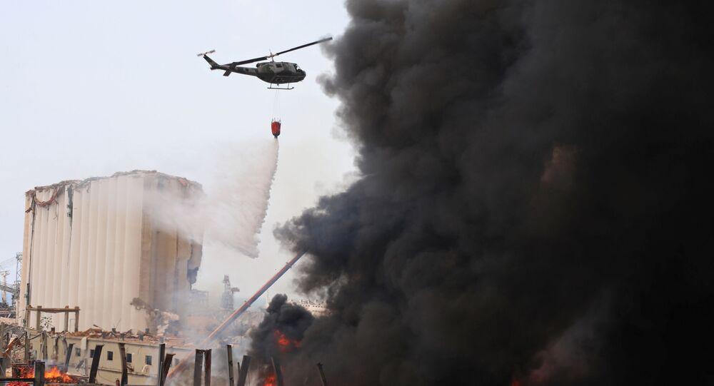 Beyrut Limanı'ndaki yangın söndürme çalışmalarına katılan Lübnan ordusundan bir helikopter su dökerken
